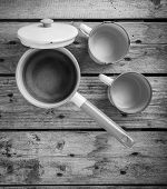 foto of saucepan  - Old cups and saucepan in a retro kitchen table setting in black and white - JPG