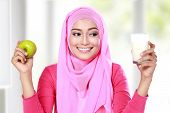 stock photo of muslimah  - portrait of young muslim woman holding an apple and a glass of milk - JPG