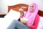 image of muslimah  - portrait of young woman enjoy watching television while eating popcorn on bed - JPG