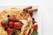 White Plate Full Of Pancakes With Raspberries Strawberries Blueberries And Honey
