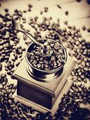 pic of threshing  - Coffee grinder with coffee grains on a wooden table - JPG