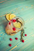 refreshing detox water with fruits in jar on wooden table