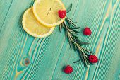 Lemon slices, raspberry and rosemary on turquoise wooden desk, close-up