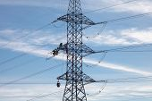 foto of electricity pylon  - High voltage electricity pylon with workers on it building up a new power line on blue sky background with clouds - JPG