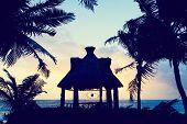 tropical pavillion on the beach at sunset