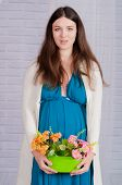 Young pregnant woman in a turquoise dress with  flowers