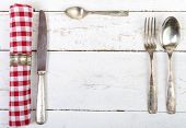 Silver Cutlery With Red Towel On An Old White Table
