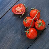 twig red tomatoes on a wooden surface