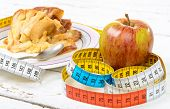 A Pastry And Apple With  A Measuring Tape