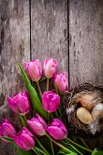 Bouquet Of Pink Tulips With A Nest With Eggs On A Wooden Background