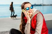 picture of dog clothes  - Sport woman dressed in warm clothes resting with phone and headphones after the excercise on the promenade in Spring - JPG