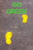 Yellow Footsteps On Sidewalk Towards Go Green Message