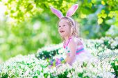 stock photo of baby easter  - Adorable curly toddler girl wearing bunny ears playing with Easter eggs in a white basket sitting in a sunny garden with first white spring flowers - JPG