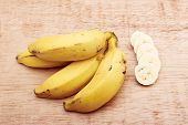 pic of bunch bananas  - Banana bunch and sliced bananas in wood background - JPG