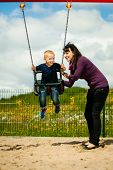 stock photo of swing  - Mother and her little son having fun together at the playground. Child kid playing on a swing. Happy healthy childhood.