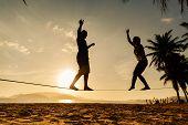 Teenage Couple Balancing Slackline On The Beach poster