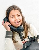 image of 7-year-old  - Seven year old girl with old vintage phone before white background - JPG