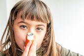 stock photo of inhalant  - Seven year old girl breathing asthmatic medicine healthcare inhaler - JPG