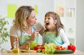 mom feeding kid daughter vegetables in kitchen