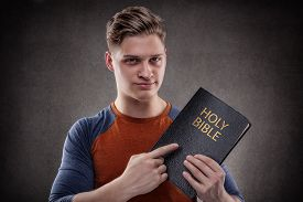 pic of holy  - Happy young man pointing his Holy Bible with leather covers - JPG