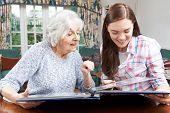 stock photo of granddaughters  - Grandmother Looking At Photo Album With Teenage Granddaughter  - JPG