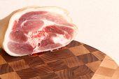 stock photo of pork chop  - piece of pork on a wooden chopping board - JPG