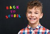 image of schoolboys  - Portrait of happy schoolboy at the black chalkboard - JPG