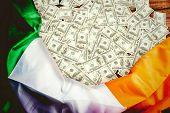 foto of irish  - Pile of dollars against irish flag on table - JPG