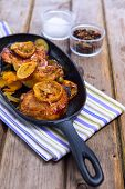 pic of thighs  - Delicious baked chicken thighs with lemon slices onion and zucchini served in cast - JPG