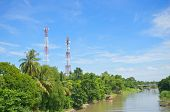 picture of antenna  - Antenna cellular mobile phone tower in forest beside river with blue sky - JPG