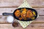 picture of thighs  - Delicious baked chicken thighs with lemon slices onion and zucchini served in cast - JPG