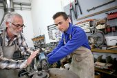 foto of ironworker  - Young man in ironworks training with professional teacher - JPG
