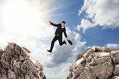 stock photo of gap  - Image of young businessman jumping over gap - JPG