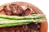 stock photo of white asparagus  - dinner of hot grilled beef meat ribs served with asparagus on wooden plate isolated on white background - JPG