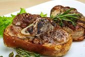 stock photo of roasted pork  - Roasted pork knee with thyme rosemary and salad leaves - JPG