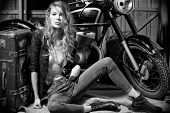 image of old suitcase  - Attractive sexual young woman in lace blouse and jeans sitting near old fashioned motorcycle with aged suitcase in garage on grey wooden wall background black and white horizontal picture - JPG