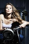 stock photo of vest  - Beautiful sensual young girl in white vest sitting on old fashioned motorcycle in garage on grey wooden wall background vertical picture - JPG