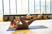 pic of leotard  - Profile of Healthy Brunette Woman Wearing Leotard Practicing Pilates on Floor Mat in Bright Exercise Studio - JPG