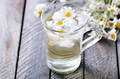 picture of chamomile  - Glass of cold chamomile tea with ice cubes and chamomile flowers on color wooden background - JPG