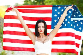 stock photo of independent woman  - Sexy woman holding USA flag outdoor independence day 4th of july - JPG