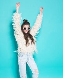 stock photo of crazy face  - studio portrait of cheerful fashion hipster girl going crazy making funny face and dancing - JPG