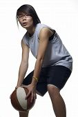 Asian female basketball player in defense