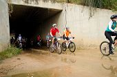 Group of riders exiting a tunnel