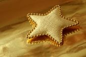Shiny gold fabric star on metallic gold wrapping paper with reflections.