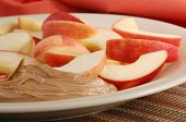 Close-up of freshly sliced apples and peanut butter on plate with color coordinated napkin as backgr