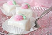 Elegant petit fours on a crystal plate with cake server.  Background of pastel pink tissue paper.  C