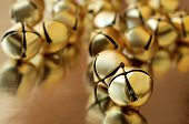 tiny gold jingle bells reflecting on metallic gold paper.  Macro with extremely shallow dof.  Select