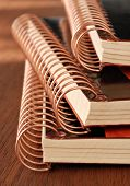 Stack of spiral bound notebooks on wood desk.  Macro with extremely shallow dof.
