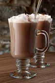 Hot chocolate or coffee latte in irish coffee mugs with stone wall in background.  Macro with extrem