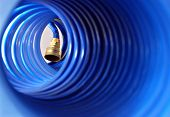 Abstract image of blue coiled garden hose with selective focus on metal hook-up.  Shallow dof.